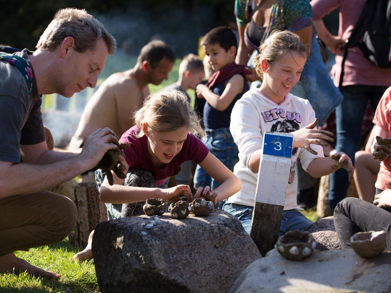 Kinderen actief met klei aan het werk om archeologische vondsten na te maken