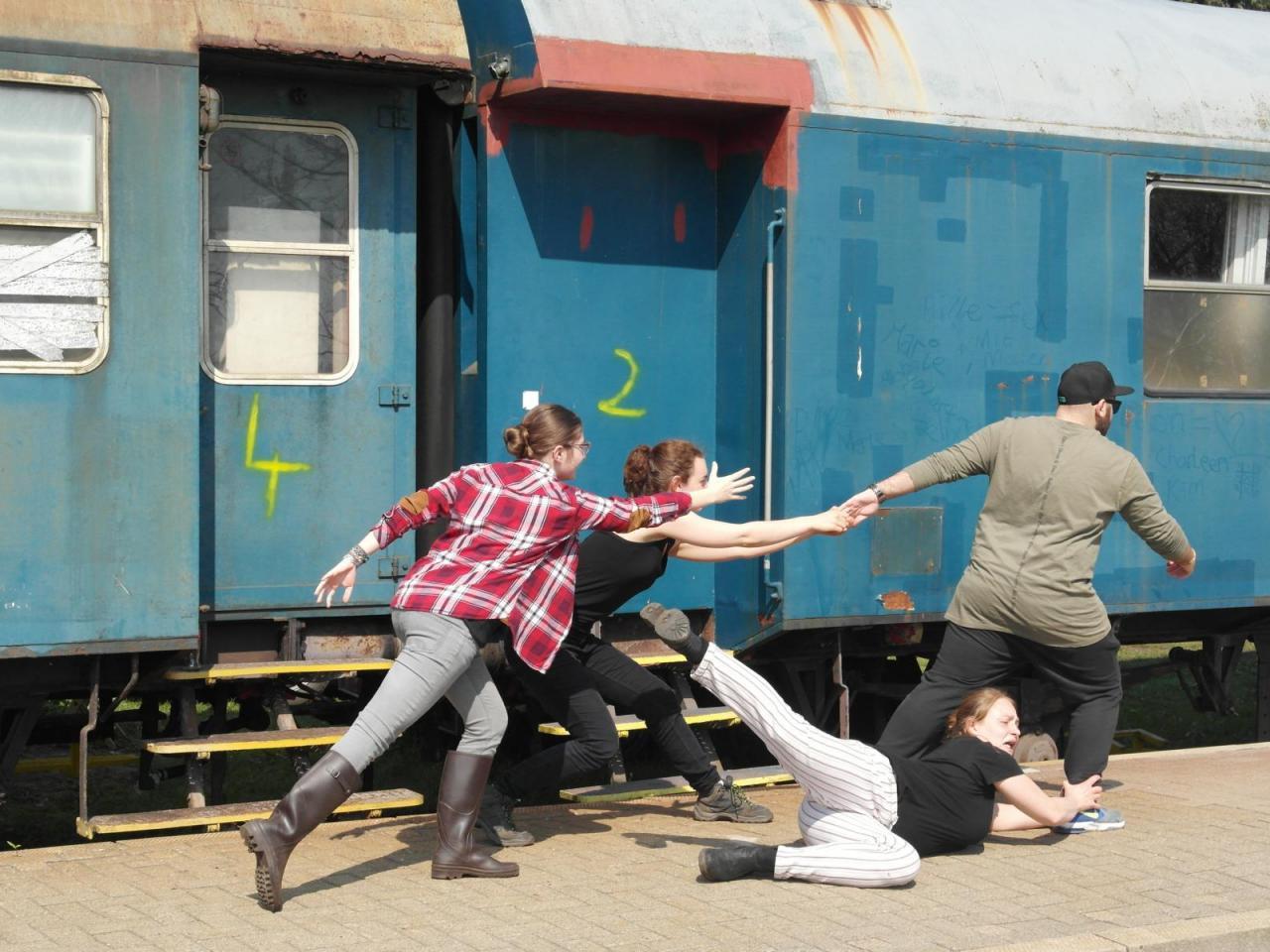 Afbeelding van jonge toneelspelers bij een trein