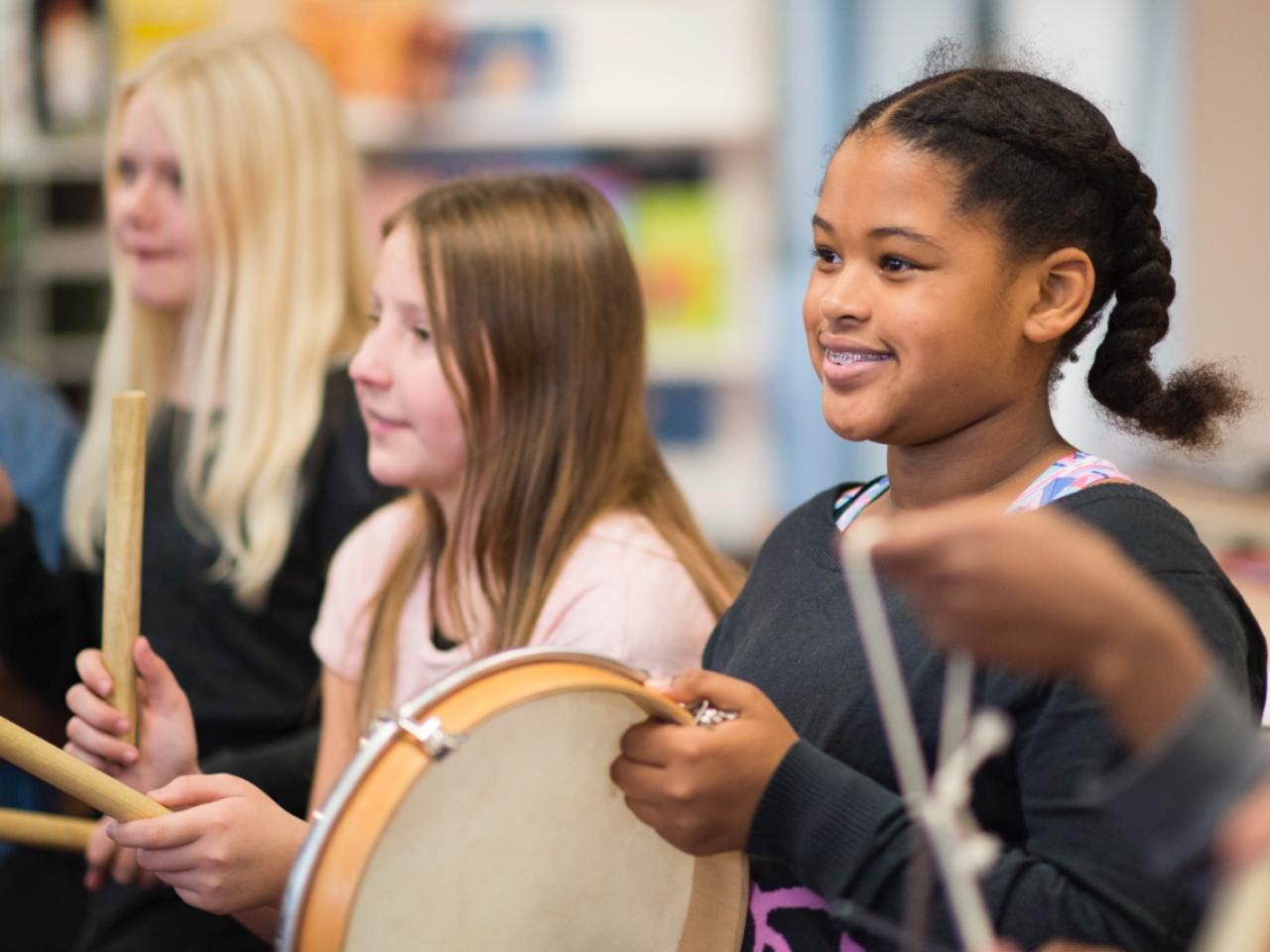 Meisje met tamboerijn in de klas