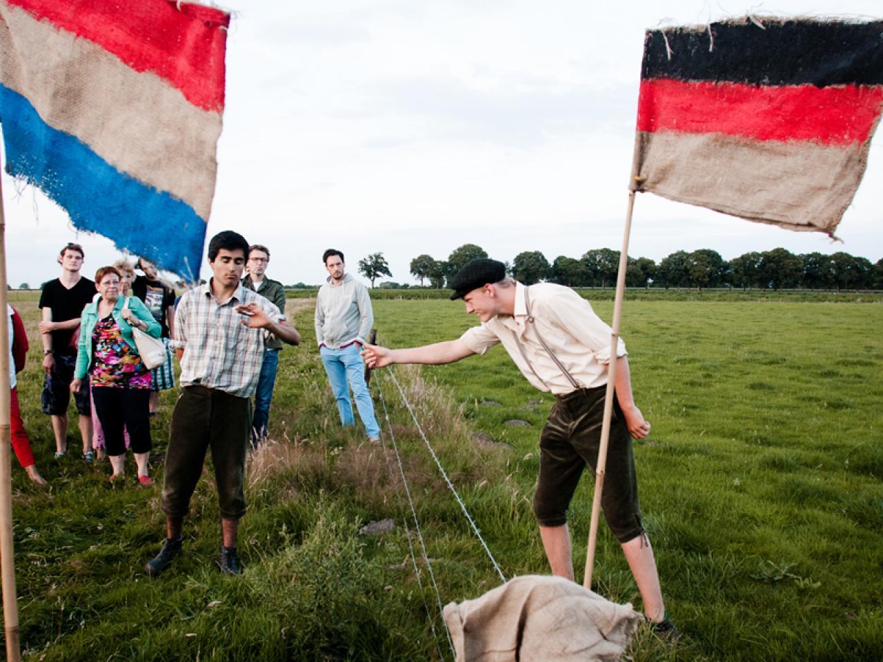 Theaterstuk op het platteland met de Nederlandse en Duitse vlag
