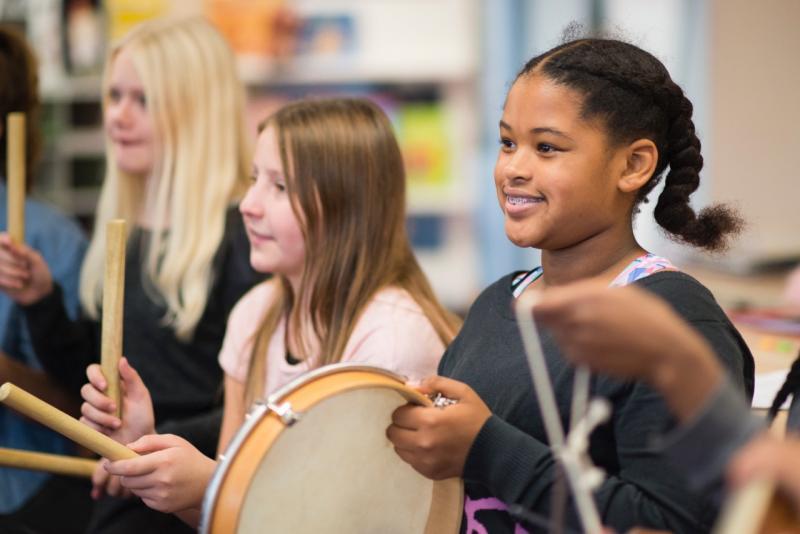 Meisje in de klas met een tamboerijn