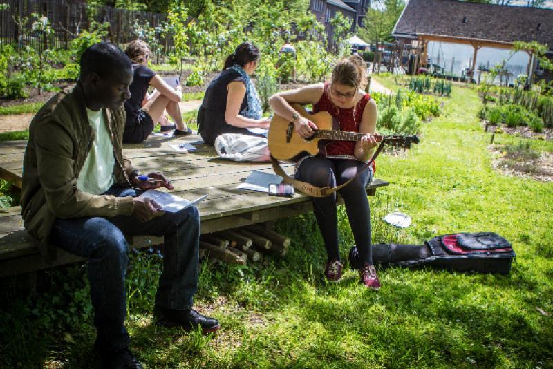Deelnemers ontspannen en maken muziek tijdens het project Literatour