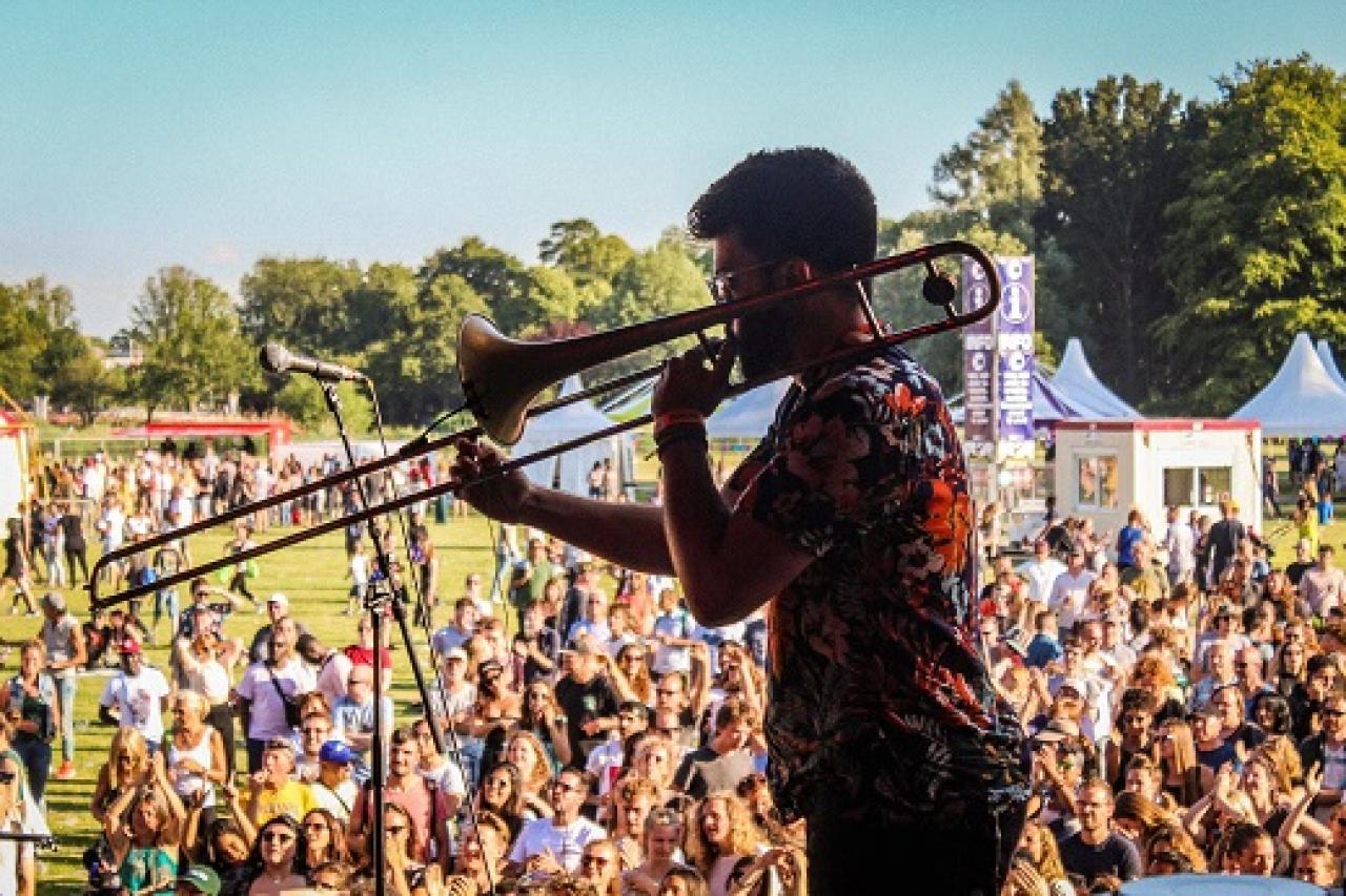 Deelnemer speelt trombone op podium van het Haags Veld op Parkpop. Fotografie: Nadege Dosso