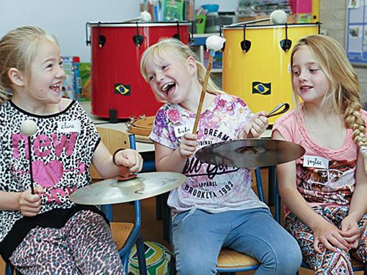 Drie drummende kinderen in de klas. Foto Henriette Guest