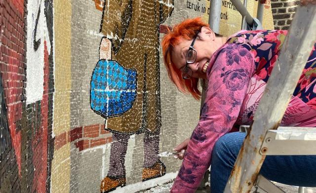 Een wijkbewoner werkt aan een mozaïek over het mijnverleden